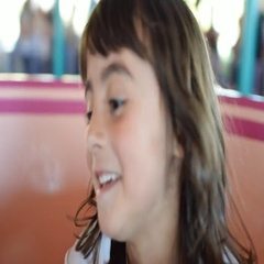 Girl on merry-go-round playground Stock Footage