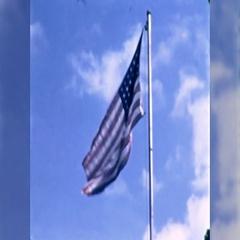 American Flag Waves Flying Flag Pole Pride US 60s Vintage Film Home Movie  Stock Footage