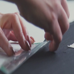 Close-up of a seamstress pursuing a line for drafting clothes. Atelier Stock Footage