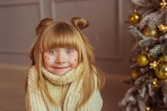 Portrait of a charming little girl in beige sweater makes faces in Christmas Stock Photos