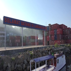 4k Container harbor panning shot with blending sun Flores island Indonesia Stock Footage