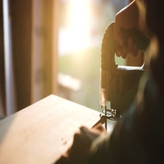 Hands of carpenter with circular saw cutting piece of wood. sun flare on Stock Footage