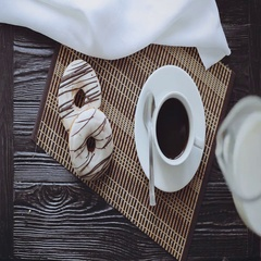 Man Pouring Milk into Coffee, Two Donuts on a Black Wooden Table, Top view Stock Footage