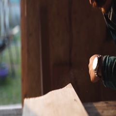 Close-up view of men working with electric jigsaw and wooden plank. sun flare on Stock Footage