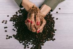 Close-up of female hands coated with scrub and coffee beans Stock Photos