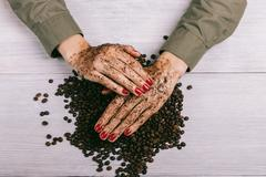Women's hands with red nail polish applied the coffee scrub Stock Photos