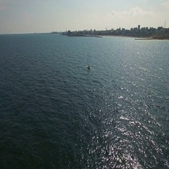 Aerial flight over sailboat at Black Sea with city coastline on the backgroun Stock Footage