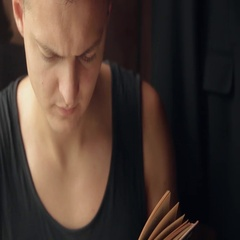 Young man read a book sitting at the window at home close-up Stock Footage