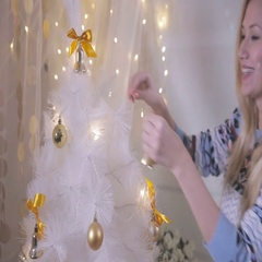 Beautiful girl decorating the New Year tree Stock Footage