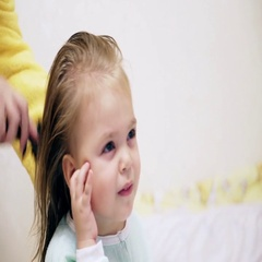 Mom combing and dry hair of a blonde little girl Stock Footage
