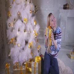 Christmas presents. Emotional pretty girl near christmas tree shows present Stock Footage