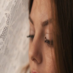 Girl with beautiful make-up looking at the camera through the fabric Stock Footage