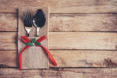 Christmas table place setting and silverware on wood with space. Stock Photos