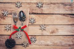 Christmas table place setting and silverware, snowflakes, pine cones on wooden b Stock Photos