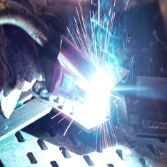 Man welding metal with bright sparks in an industrial plant Stock Footage