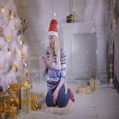 Pretty girl use mobile phone, sitting near Christmas tree during Christmas Eve Stock Footage