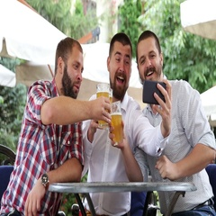 Three men sitting in cafe, drinking beer and making photo by tel Stock Footage