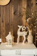 Interior room with a deer, a lamp and a garland on the background of wooden wall Stock Photos