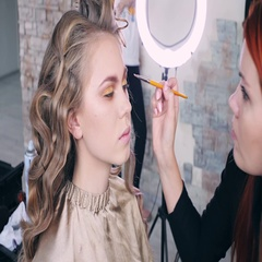Makeup artist makes models eye makeup. Hairdresser makes hairstyle for model Stock Footage
