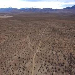 Aerial desert landscape bird-eye view flying backwards over desert road 4k Stock Footage