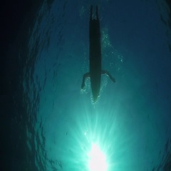 SLOW MOTION UNDERWATER: Female surfer paddling on a surf in open water ocean Stock Footage