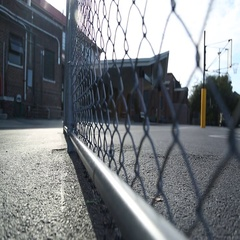Empty school yard, chain link fence, basketball goal Stock Footage