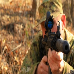 Soldier (or strikeball player) in ambush, looking through the scope. Stock Footage