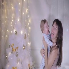 Mother and baby laughing, having fun near decorated new year tree full of Stock Footage
