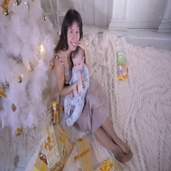 Christmas family concept. Mom Feeding her Baby near Christmas Tree during new Stock Footage