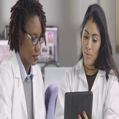 Two women in lab coats looking at an ipad computer Stock Footage