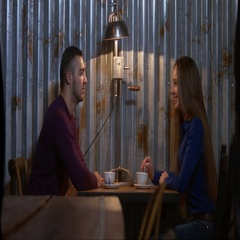 4K CINEMAGRAPH - couple sitting in a cafe, girl stirring coffee. Seamless loop Stock Footage