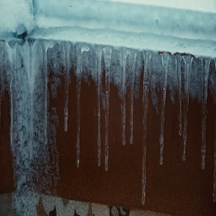 Multiple icicles against brown wall Stock Footage