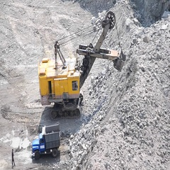 Huge excavator and truck and a man granite quarry Stock Footage