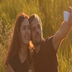 Romantic couple walking in the Park at sunset and makes a selfie Stock Footage