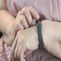 Woman touches on the wristband of pulse monitor Stock Footage