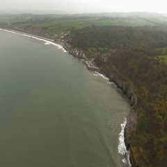 Rocky coastline with resort town in the distance flyby shot. Aerial view Stock Footage