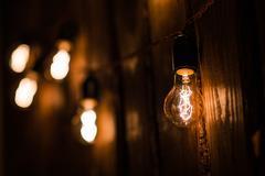 Vintage incandescent Edison type bulbs on wooden wall Stock Photos