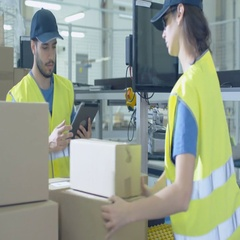 Post Sorting Center Worker Puts Cardboard Boxes on Belt Conveyor while Another W Stock Footage