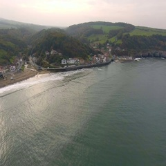 Beautiful resort town reveal shot. North Sea, North Yorkshire, UK. Aerial view Stock Footage