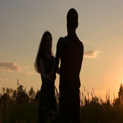 Beautiful swirl couple holding hands. At sunset. Stock Footage