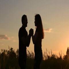 Beautiful loving couple holding hands looking at each other. At sunset. Stock Footage