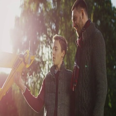 Father and Son Inspecting Model Airplane in the Park and Planning to Launch it. Stock Footage