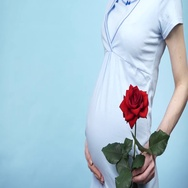 Pregnant woman holds rose flower and caressing her belly 4K Stock Footage