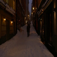 People walking in a narrow slippery uphill street during night in a snowy day Stock Footage