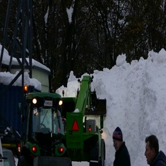 Excavator clearing a huge amount wall of snow from road to unblock the roadway Stock Footage