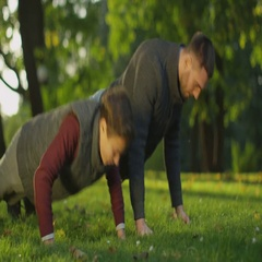 Father and Son Doing Push-ups in the Park. Stock Footage