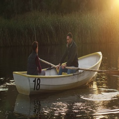 Father and Son on the Boat. Father is Rowing while Son fishes. Stock Footage
