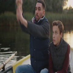 Father and Son Sitting in the Boat Fishing. Father Swings Fishing Rod. Stock Footage