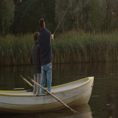 Father and Son are Standing in the Boat and Fishing. Stock Footage