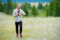 Man uses a smart watch during the run in the mountains Stock Photos